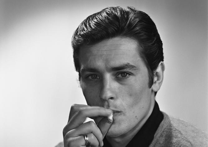 Photo studio : portrait de face souriant d'Alain DELON fumant une cigarette.