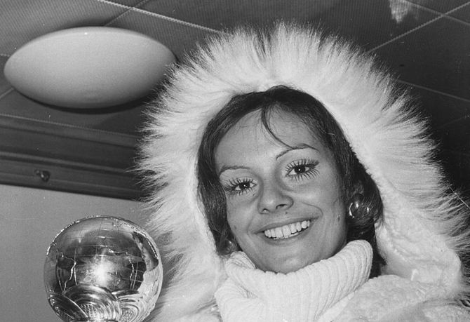 Newly crowned 'Miss World' winner Lucia Petterle from Brazil is holding her trophy and smiling, wrapped up against the cold as she prepares to fly home from Heathrow Airport, London, November 21st 1971. (Photo by Keystone/Hulton Archive/Getty Images)