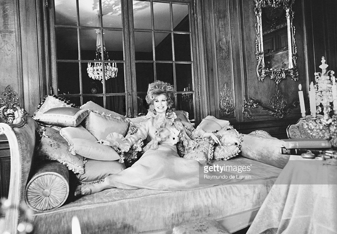 Gossip columnist Suzy (aka Mrs. Aileen Mehle), reclining on an oversized couch with many pillows in the drawing room of her New York mansion *** Local Caption *** Aileen Mehle;